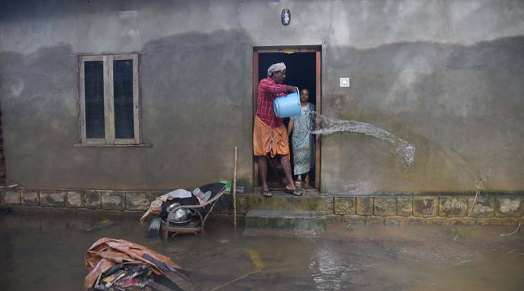 Man pours water out of flooded home