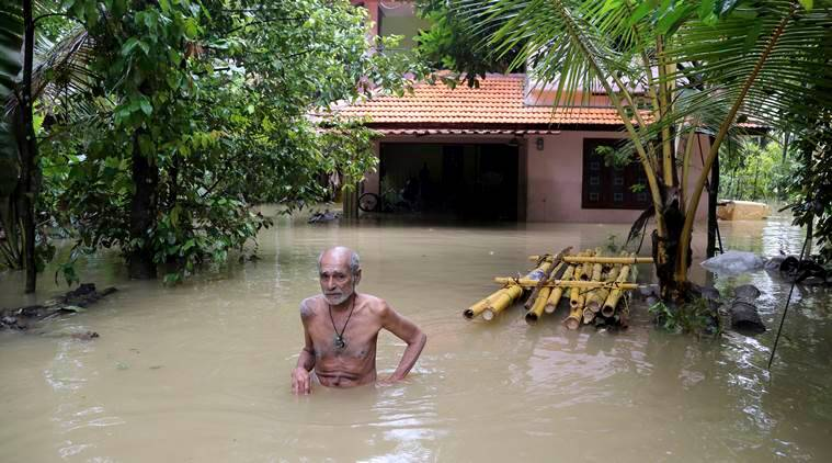 Man wades through flooded home in Kerala