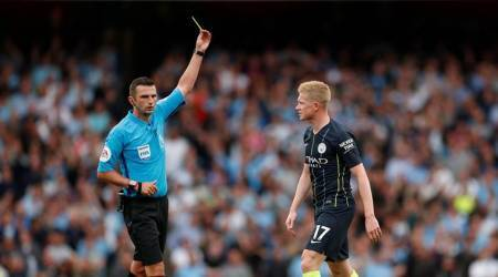 Manchester City's Kevin De Bruyne is booked by referee Michael Oliver as Arsenal's Lucas Torreira lies injured