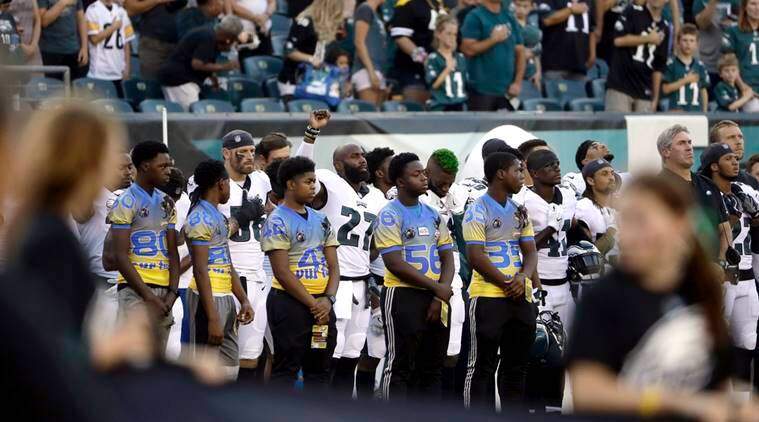 Philadelphia Eagles' Malcolm Jenkins, center left, raises his fist during the national anthem before the team's preseason NFL football game against the Pittsburgh Steelers.