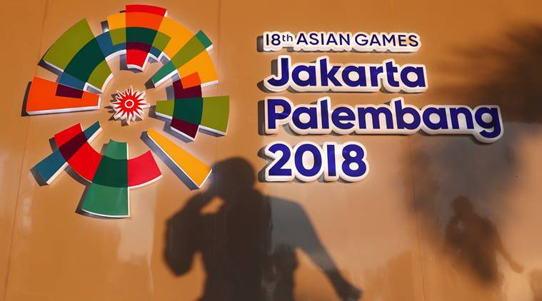 A man passes a signage at the media center ahead of the Asian Games in Palembang, South Sumatra, Indonesia