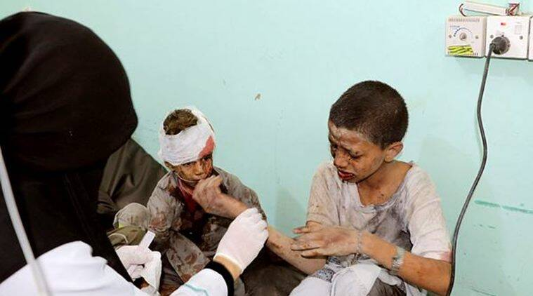A doctor treats children injured by the airstrike. (Reuters)