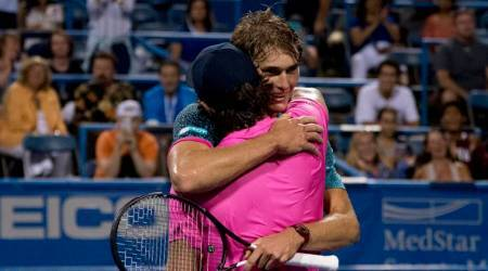 Alexander Zverev, of Germany, smiles as he hugs his brother Mischa Zverev, of Germany, foreground, after defeating him 6-3, 7-5, during the Citi Open tennis tournament in Washington