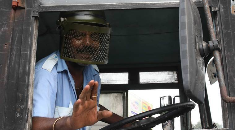 A bus driver wears a helmet to protect himself from stone pelters in Kolkata. (Express photo/Partha Paul)