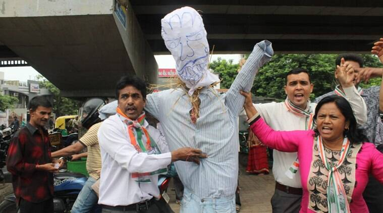 Congress workers protest along with an effigy in Ahmedabad on Monday. (Express photo/Javed Raja)