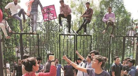 Protesting journalism students climb gate in Delhi University