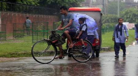 Students on their way to school during the light rain showers in sector 25, Chandigarh, on Wednesday. (Express photo/Sahil Walia)