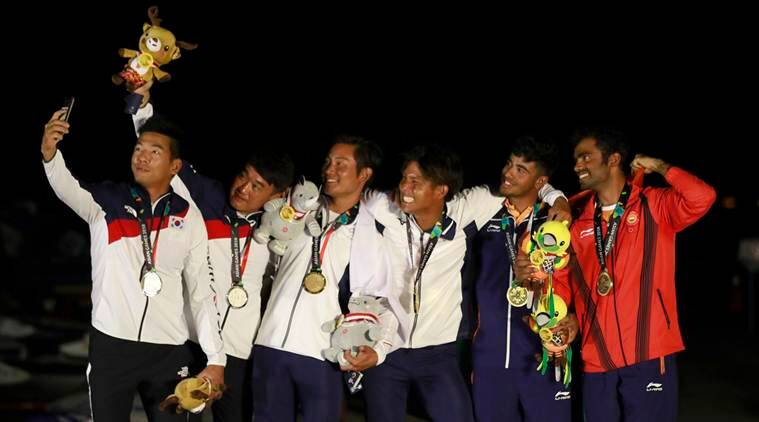From left to right silver medalist Chae Bonjin and Kim Dongwook of Korea, gold medalist Shingen Furuya and Shinji Hachiyama of Japan and bronze medalist Varun Ashokthakkar and Kelapanda Chengappa of India pose for a selfie with their medals during the victory ceremony for in the 49er Men of sailing event at the18th Asian Games in Jakarta, Indonesia