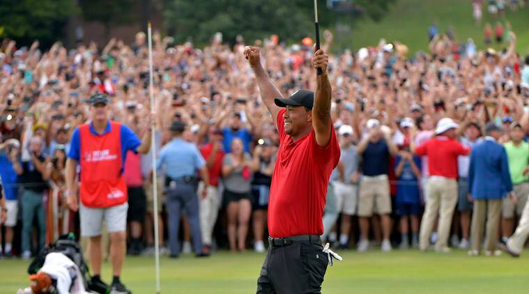 Tiger Woods celebrates after picking up his putt for par on the 18th green to win the final round of the Tour Championship golf tournament Sunday, Sept. 23, 2018, in Atlanta.