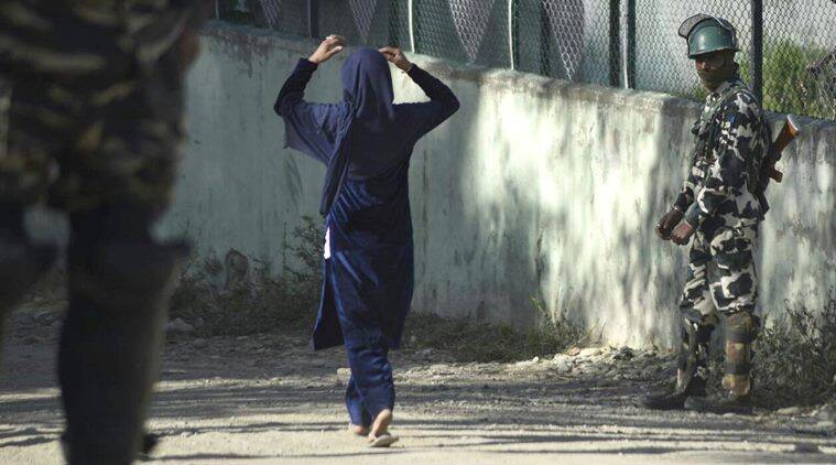 Security personnal stand as kashmiri woman walk near a poling station in Bandipora during voting began for the first phase of the urban local bodies (ULB) elections in Jammu and Kashmir.Express Photo by Shuaib Masoodi 08-10-2018