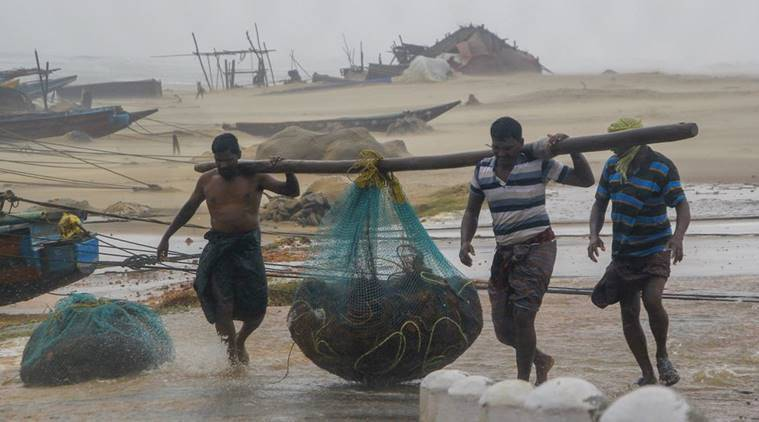 Fishermen engaged in their work as Cyclone Titli hits the coast starting with surface wind effect reaching speeds of 126 kmph at Gopalpur, in Ganjam. (PTI photo)