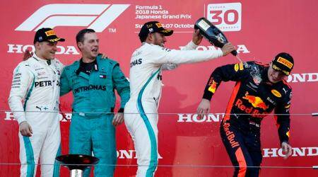 Mercedes' Lewis Hamilton celebrates winning the race on the podium with second placed Mercedes' Valtteri Bottas and third placed Red Bull's Max Verstappen