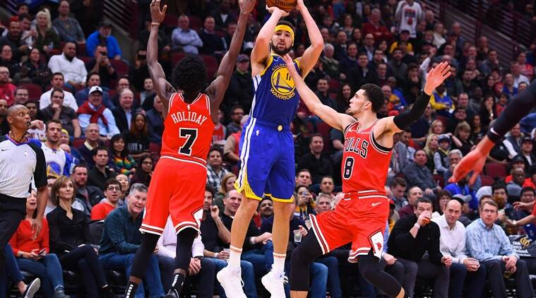 Golden State Warriors guard Klay Thompson (11) shoots the ball against Chicago Bulls forward Justin Holiday (7) and guard Zach LaVine (8) during the second half at the United Center.