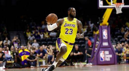 Los Angeles Lakers forward LeBron James dribbles during the first half of an NBA preseason basketball game against the Denver Nuggets