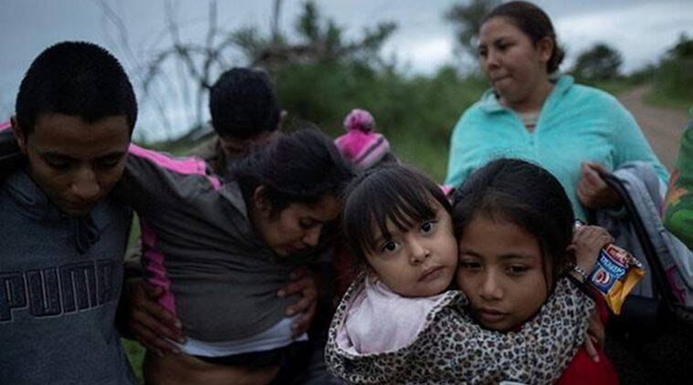 Crystal, 5, of Honduras, is held by her sister after a group of two dozen families members raced away from what border patrol agents said were gunshots near the site where they illegally crossed the Rio Grande river into the United States from Mexico in Fronton, Texas. (Reuters)