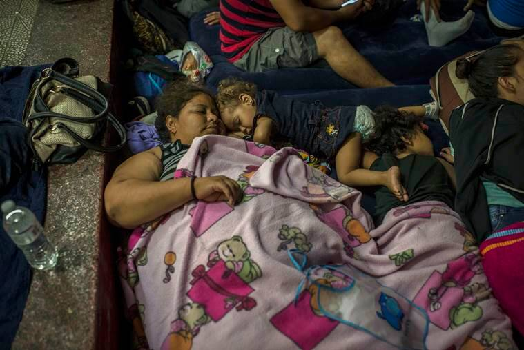 Lindell Marroquin of La Ceiba, Honduras, rests with her two daughters at a school in Guatemala City.