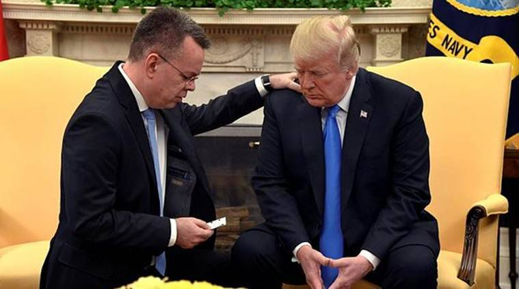 US President Donald Trump closes his eyes in prayer along with Pastor Andrew Brunson, after his release from two years of Turkish detention, in the Oval Office of the White House, Washington. (Reuters)