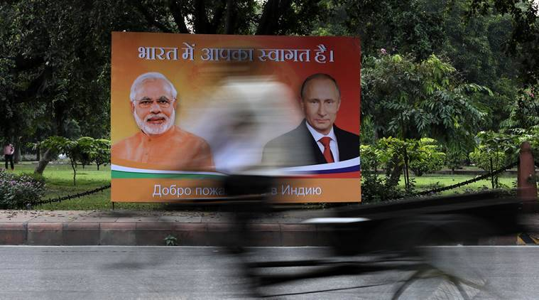 A man pedals his trishaw in front of a hoarding showing images of Russian President Vladimir Putin and India