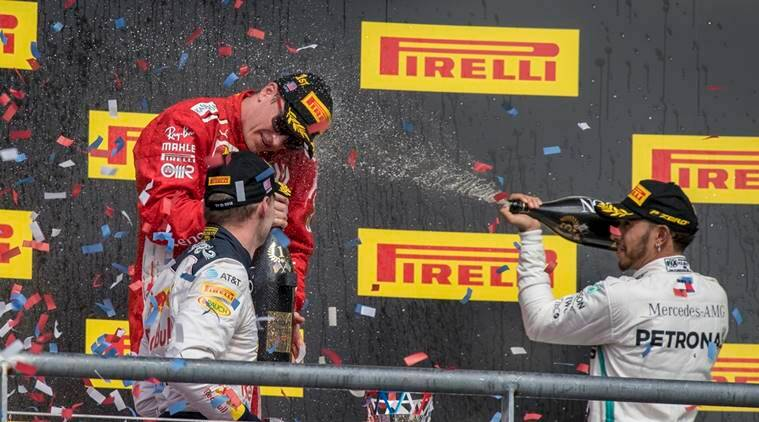Ferrari driver Kimi Raikkonen (center) of Finland celebrates winning the United States Grand Prix at Circuit of the Americas with Red Bull Racing driver Max Verstappen (left) of Netherlands and Mercedes driver Lewis Hamilton (right) of Great Britain