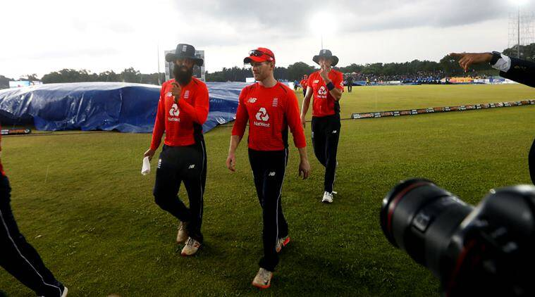 England's captain Eoin Morgan (C), Moeen Ali (L) and Olly Stone walk off the field after match was stopped due to rain
