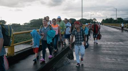 Migrants from Central America flee a sports center camp