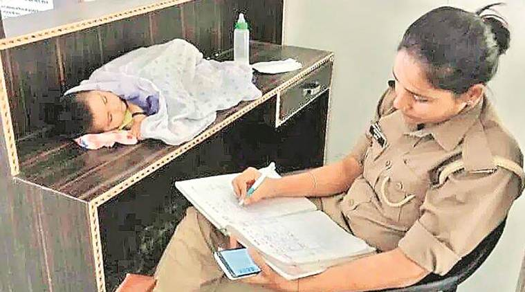 Uttar Pradesh police, woman constable with baby, Up news, Woman constable at work with baby, woman police with baby transferred, Indian express