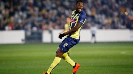 Usain Bolt smiles as he looks over his shoulder during a friendly trial soccer match between the Central Coast Mariners and the Central Coast Select in Gosford, Australia