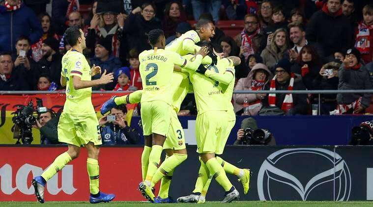 Barcelona players celebrate after Ousmane Dembele scored their first goal during a Spanish La Liga soccer match between Atletico Madrid and FC Barcelona at the Metropolitano stadium in Madrid
