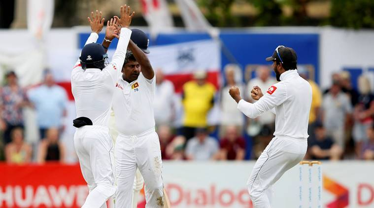 Sri Lanka's Rangana Herath (C) celebrates with Kusal Mendis (L) and captain Dinesh Chandimal after taking the wicket of England's captain Joe Root