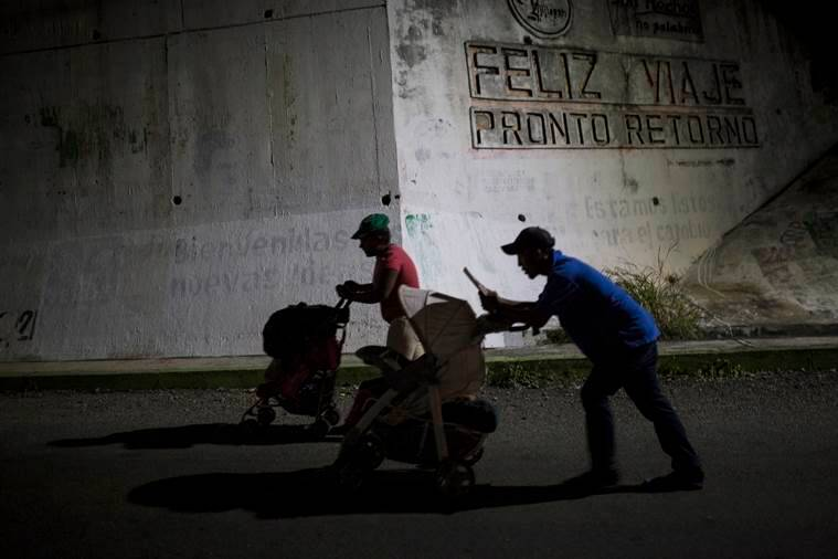 Joel Eduardo Espinar, foreground, and his wife, Yamilet Hernandez, push baby strollers as they start early in the morning towards the next town Arriaga from Pijijiapan, Mexico.