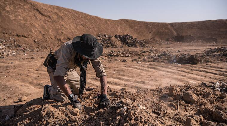 An Iraqi army soldier searches for remains at a mass grave