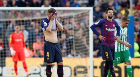 Barcelona's Ivan Rakitic and Gerard Pique looks dejected after Real Betis' second goal scored by Joaquin
