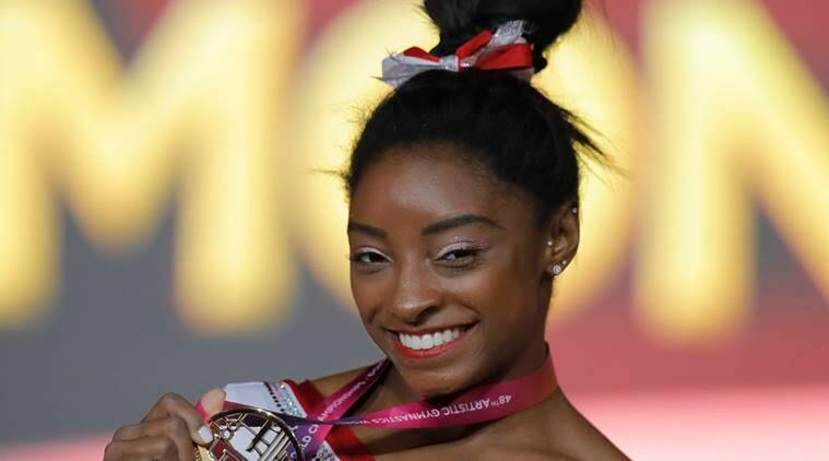Simone Biles of the U.S. shows her gold medal after the women's vault final on the first day of the apparatus finals of the of the Gymnastics World Chamionships at the Aspire Dome in Doha, Qatar