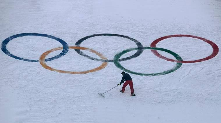 A worker grooms the snow after installing a set of Olympic Rings on the ski jump hill at the 2018 Winter Olympics at the Alpensia Ski Jumping Center in Pyeongchang, South Korea