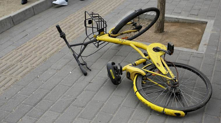 An Ofo bike-sharing bicycle is locked for personal use at a bus station on the outskirts of Beijing.