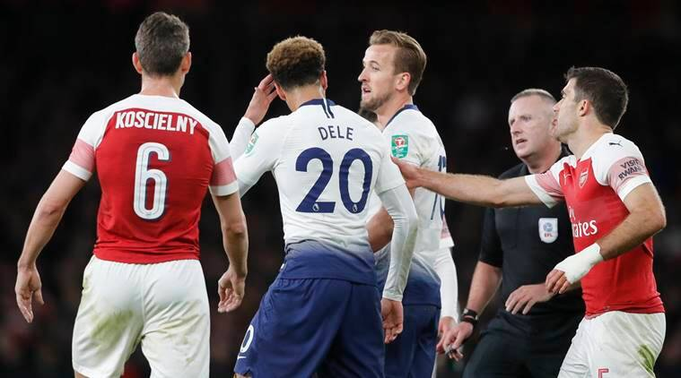 Tottenham's Dele Alli, second from left, reacts after a bottle was thrown at him from the stands during the English League Cup quarter final soccer match between Arsenal and Tottenham Hotspur at the Emirates stadium in London