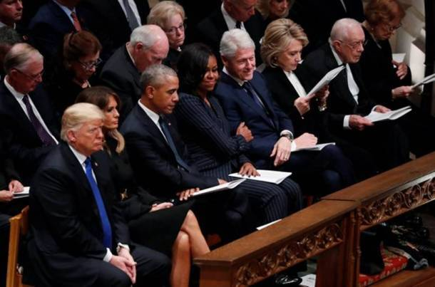 Former U.S. first lady Michelle Obama holds on to arm of former U.S. President Clinton during state funeral for former U.S. President George Bush at Washington National Cathedral