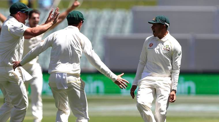 Australia's Usman Khawaja, right, celebrates with his teammates after taking a catch to dismiss India's Virat Kohli during the first cricket test between Australia and India in Adelaide