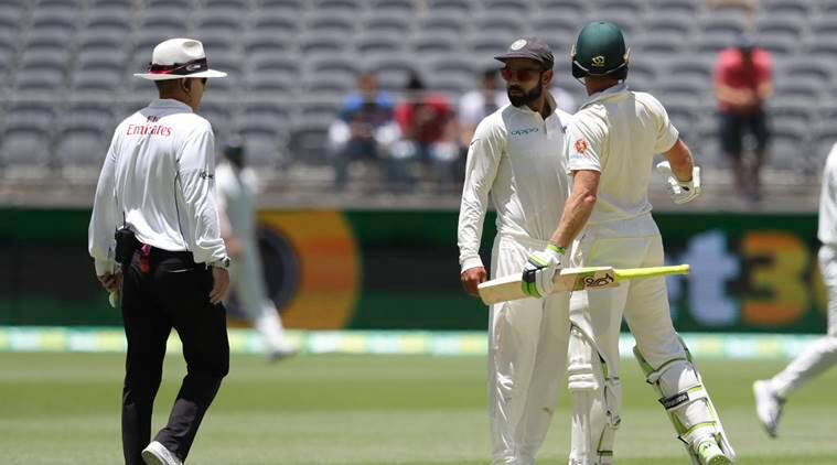 India's Virat Kohli, centre, looks to the umpire after he and opposing captain, Australia's Tim Paine came face to face after Kohli moved into Paine's path during play in the second cricket test between Australia and India in Perth, Australia