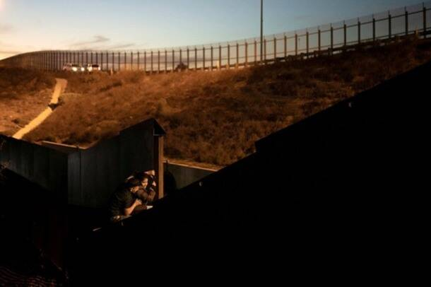 Migrants, part of a caravan of thousands from Central America trying to reach the United States, climb a border fence as they try to cross illegally from Mexico to the U.S, in Tijuana