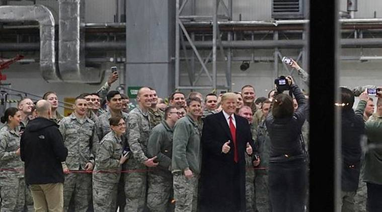 US President Donald Trump is seen through glass as he takes a photo with US troops at Ramstein Air Force Base in Germany on Thursday. (Reuters)