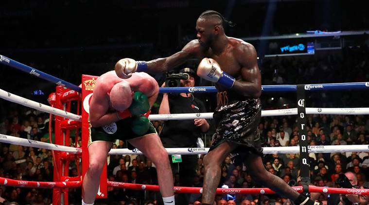 Deontay Wilder knocks down Tyson Fury during their heavyweight boxing bout