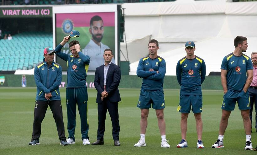 Australian team members stand by as India's Virat Kohli accepts the winners trophy after play was called off on day 5 of their cricket test match in Sydney