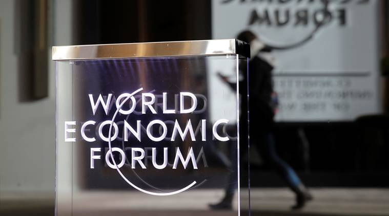 A person passes by a World Economic Forum logo in Davos, Switzerland.