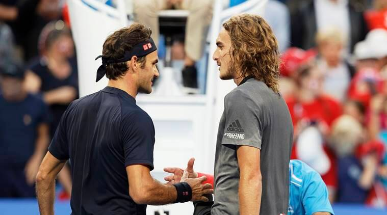 Switzerland's Roger Federer, left, shakes hands with Stefanos Tsitsipas of Greece at the net after winning their match at the Hopman Cup in Perth, Australia