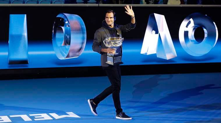 Defending men's champion Switzerland's Roger Federer holds the Norman Brookes Challenge Cup as he leaves Margaret Court Arena follwoing the official draw ceremony ahead of the Australian Open tennis championships in Melbourne, Australia