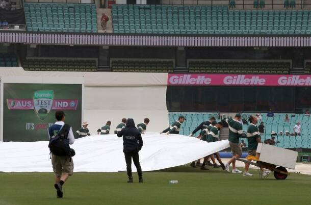 Grounds crew pull a tarpaulin over the pitch as rain falls during a delay before play on day 5 of the cricket test match between India and Australia in Sydney