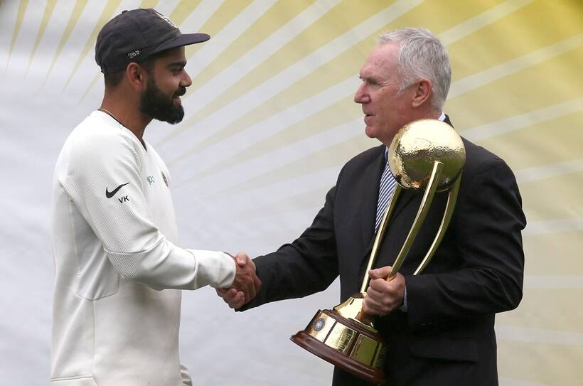 India's Virat Kohli, left, is presented the Border–Gavaskar Trophy by Allan Border after their series win over Australia after play was called off on day 5 of their cricket test match in Sydney