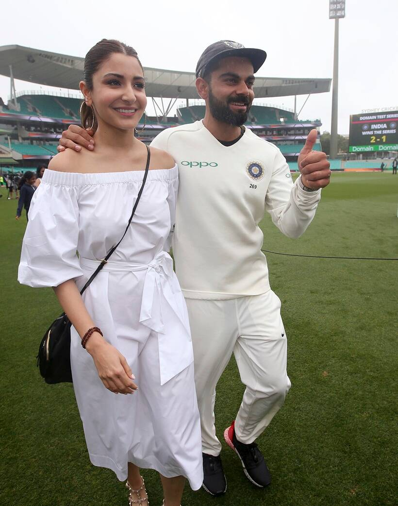 India's cricket captain Virat Kohli, right, walks with his wife, Anushka Sharma celebrates India's series win over Australia after play was called off on day 5 of their cricket test match in Sydney