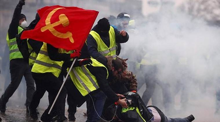 "Protesters wearing yellow vests help a person injured by a water cannon during a demonstration by the ""yellow vests"" movement near the Arc de Triomphe in Paris. (Reuters)"